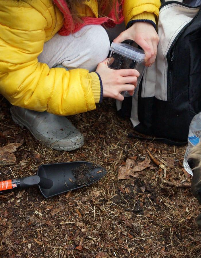 kid naturalist digging up sample