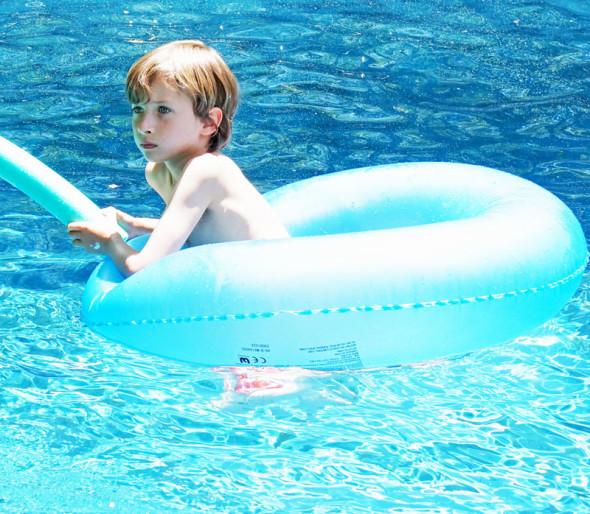 Sitting in blue ring in blue water in pool