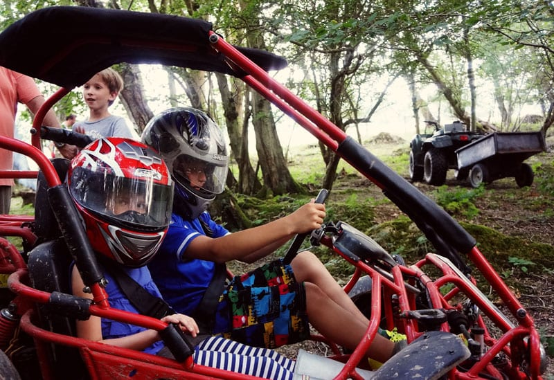 off road go kart with kids in woods