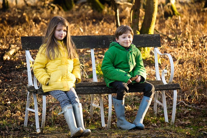 Luce and Theo on bench grinning
