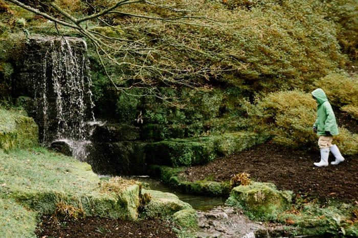 Theo by waterfall at Wakehurst