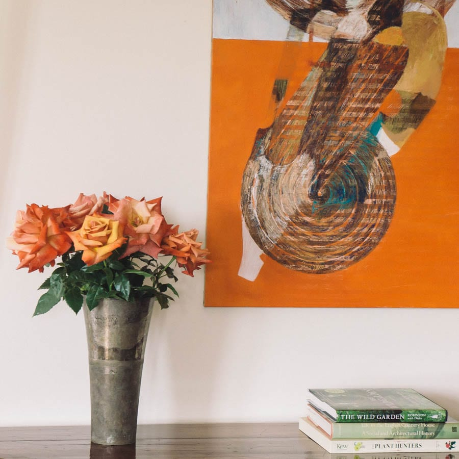 Orange red roses in vase with painting_