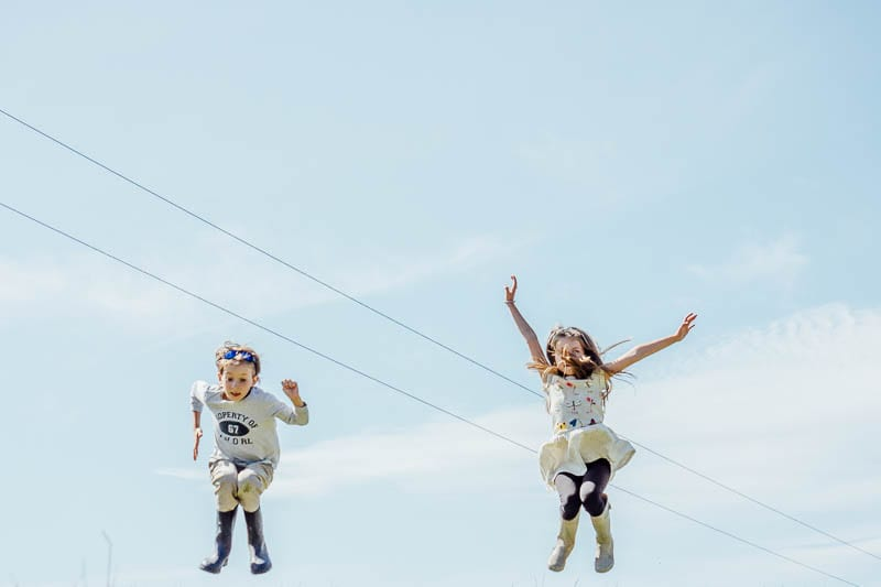 Twins in August jumping in sky