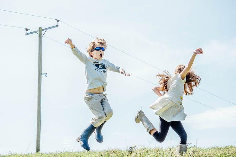 Twins in August leaping in joy