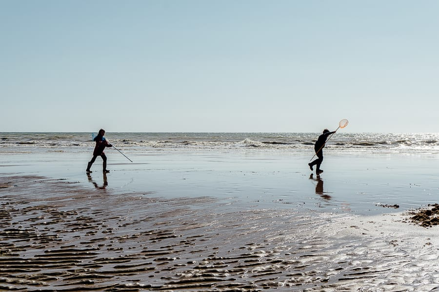 Rock pooling kids and waves and nets